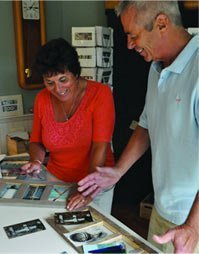 Chris and Jan Capece building a sign and selecting photos